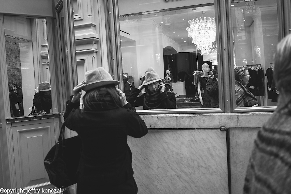 A women takes a look at herself in a mirror while trying on a hat in the GUM shopping center near red square Moscow, Russia.