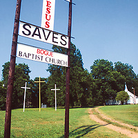 Bernard Coffindaffer, businessman turned evangelist, financed the building of groups of 3 crosses across 29 states. This trio is perfectly framed by the Bogue Baptist Church sign, and stands along Highway 49.