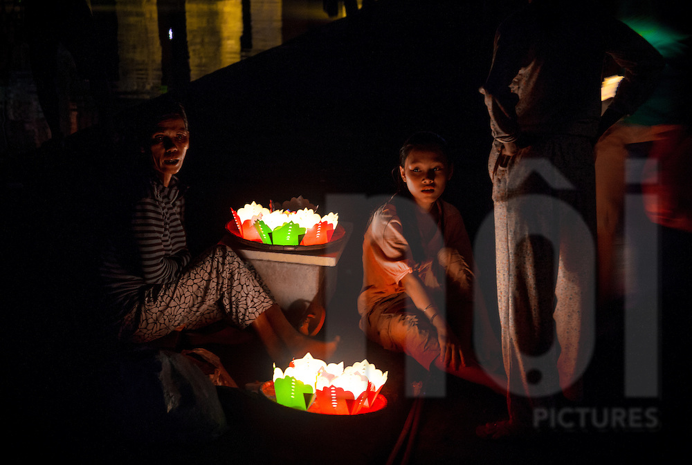 Vietnamese people sellling candles at night in Hoi An, Vietnam, Asia