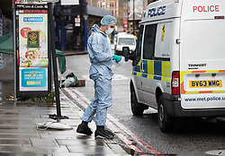 © Licensed to London News Pictures. 18/08/2017. London, UK. A police forensics officer collects evidence in Atlantaic road after man died from stab wounds after an incident in Brixton. Police launched a murder investigation after being called at 12:50 hrs today. Photo credit: Peter Macdiarmid/LNP