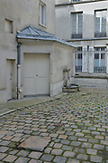 Paving stones with 'pave a fendre', and a water pump, at 52 Rue de l'Arbre Sec, in the 1st arrondissement of Paris, France. The pave a fendre or cracked paver, is a paving stone larger than the surrounding ones, used to split the logs which were delivered in the streets for fuel for houses. People split the long logs outside on these larger stones to avoid damaging the cobblestones. This practice was in place from the 17th century. Picture by Manuel Cohen