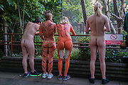 Runners look in the monkey enclosure - Naked runners take part in the ZSL London Zoo Streak for Tigers. They are raising money for tigers whose group name is, apparently, a streak.
