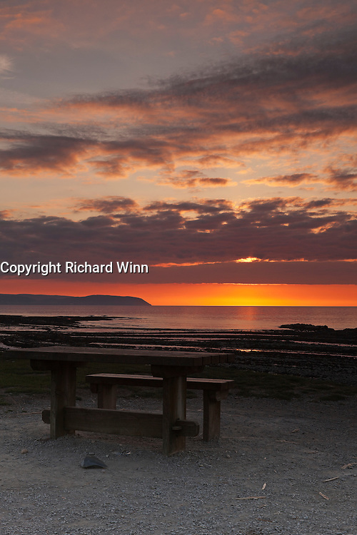 Kilve beach close to sunset, with the sun poking through the clouds over the Bristol Channel and the picnic table in the foreground. In portrait format.