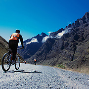 "Mountain Biking on Death Road, Bolivia...A tour group of Mountain Bikers make their way along tarmac road past breathtaking scenery as they travel along the first part of their journey heading towards the notorious jungle strip of 'Death Road'...The North Yugas Road is a 64 Kilometer road leading from La Paz to Corioico. It is legendary for it's extreme danger and in 1995 the Inter American Development Bank christened is as the ""world's most dangerous road"".. The road was built in the 1930's during the Chaco War by Paraguayan prisoners to connect the Amazon rainforest region of Northern Bolivia to it's capital City La Paz. One estimate is that 200 to 300 travelers were killed yearly along the road. On 24 July 1983, a bus veered off the Yungas Road and into a canyon, killing more than 100 passengers in what is said to be Bolivia's worst road accident..A new stretch of the La Paz-Coroico highroad was opened in 2006 to bypass the notorious stretch known as death road..The danger of the road has now made it a popular tourist destination starting in the 1990's and drawing thrill-seekers and mountain bike enthusiasts who ride on the 64km mainly downhill stretch from La Cumbre, a 4,700 meter peak to Yolosa, a decent of 3600 meter's (11,800 feet). The journey includes breathtaking views of snow covered peaks and towering cliffs and starts along modern asphalted road before entering the jungle itself and the most dangerous and notorious part of the ride. The infamous narrow dirt road, most of the road no wider than 3.2 meter's, is cut into the side of the mountain with sheer drops to the left of up to 600 meter's with virtually no safety rails on the winding steep decent..There are now many tour operators catering to this activity, providing information, guides, transport and equipment. Nevertheless, the Yungas Road remains dangerous. At least 13 of these cyclists died on the ride since 1998, the latest A 28-year-old Israeli traveler was killed in April 2010  the group of cy"