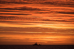 © Licensed to London News Pictures. 13/11/2016. Wick, UK.  The silhouette of a ship shortly before sunrise in the Moray Firth in Scotland this morning, remembrance sunday, 13th November 2016.  Photo credit: Rob Arnold/LNP