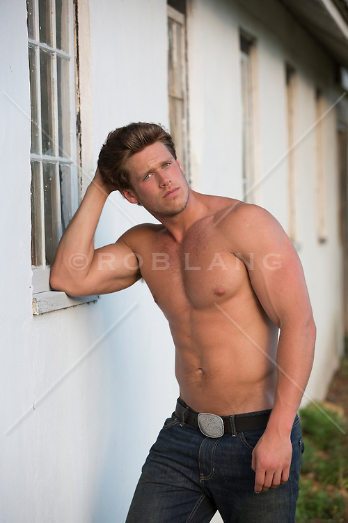 hot stud without a shirt leaning against a barn