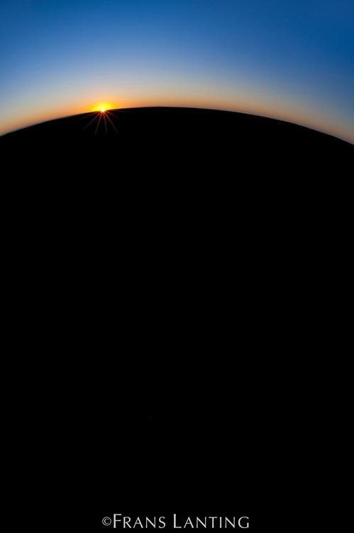 Sun setting over gravel plain, Skeleton Coast, Namibia