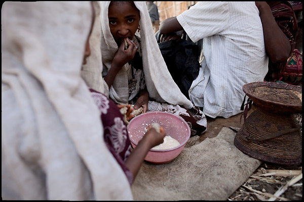 """Ishalem (left side), 6 yeras old, and Jerusalem (middle), 8 years old, eat their meal, after a long night spent awake during their marriage's celebration. Both of them are child brides and have just married with boys of 10 years largest. The festivities will extend over several days, the only way to encourage young brides is to allow them to drink tella, a local wine. Child marriage was a major issue raised by the 2007 United Nations Commission on the Status of Women. A U.S. resolution to reduce the practice was passed, encouraging countries to take actions. In Ethiopia the legal age to get married is 18, the law quite often is ignored. North West of Ethiopia, on saturday, Febrary 14 2009.....In a tangled mingling of tradition and culture, in the normal place of living, in a laid-back attitude. The background of Ethiopia's """"child brides"""", a country which has the distinction of having highest percentage in the practice of early marriages despite having a law that establishes 18 years as minimum age to get married. Celebrations that last days, their minds clouded by girls cups of tella and the unknown for the future. White bridal veil frame their faces expressive of small defenseless creatures, who at the age ranging from three to twelve years shall be given to young brides men adults already...To protect the identities of the recorded subjects names and specific places are fictional."""