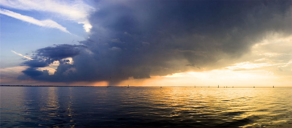 Sailboats look for the wind in front of a thunderhead.