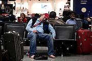 Frankfurt am Main | 18.04.2010..Durch den Ausbruch des Vulkans Eyjafjallajoekull auf Island und dadurch ausgestossene Aschewolken ist der Luftraum ueber weiten Teilen Europas f?r den Flugverkehr gesperrt, dadurch sitzen im Transit-Bereich im Flughafen Frankfurt etwa 800 Menschen fest, die kein Visum f?r Deutschland haben. Hier: Ein Fluggast hat sich Schuhe und Struempfe ausgezogen und schlaeft friedlich auf einem Sitz im Terminal 1. ..Foto: peter-juelich.com..[No Model Release | No Property Release]