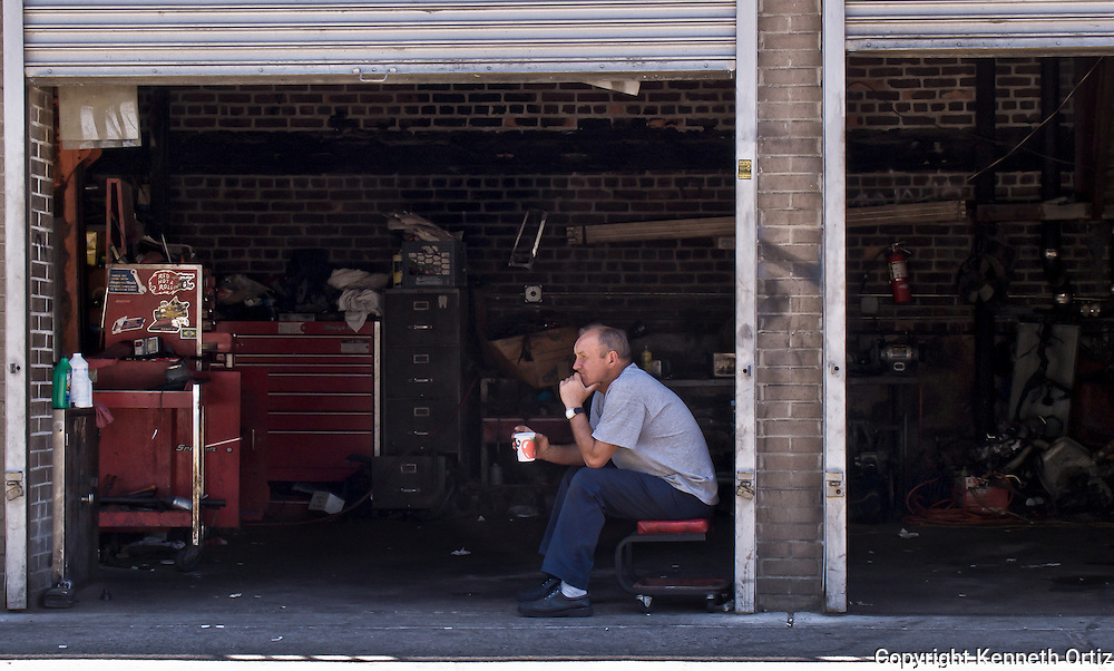 A Mechanic takes a moment during the day to take a coffee break and think.