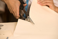 Cropped image of fashion designer cutting cloth