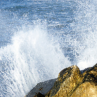 Crashing waves against concrete barrier, close-up