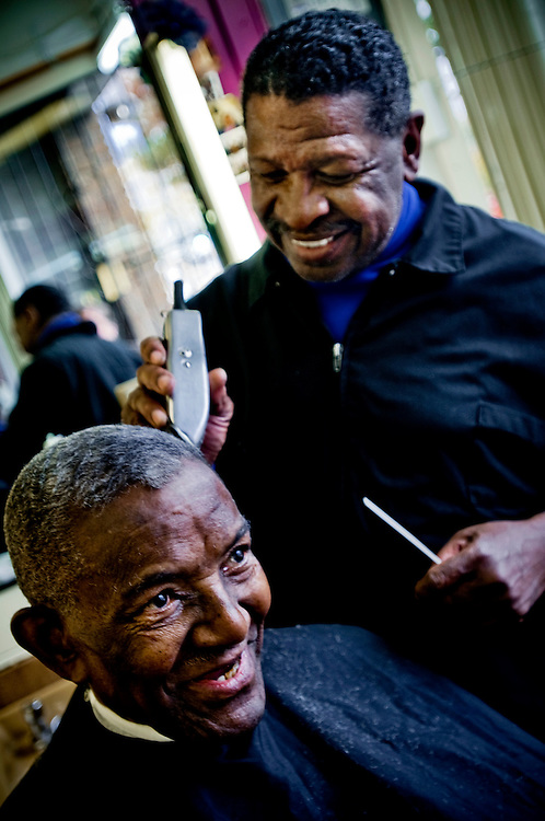 Black voters in the Washington DC neighborhood Anacostia..Clarence Brace at Brace's Barber shop giving his regular customer Henry Hampton a haircut. Henry is 88 and drove a cab in DC for 49 years. Both are Obama supporters..Photographer: Chris Maluszynski /MOMENT