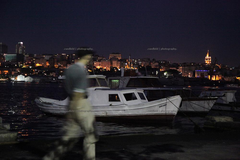 A Man walks along a Bosporus boat dock.