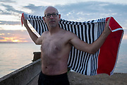 As the sun sets over fading daylight and calm waters of the Thames Estuary, a wild sea swimmer dries himself with a beach towel after his regular evening dip, on 18th July 2020, in Whitstable, Kent, England.