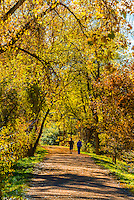 Couple walking on the Highline Canal path on an Autumn afternoon, Littleton, Colorado USA.