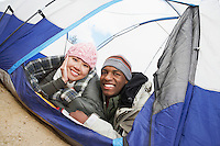 Couple in warm clothing lying down in tent