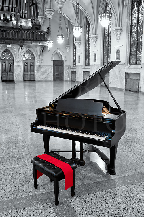 A black grand piano waits for someone to accept its invitation to come and play in this beautiful old church, one that has been converted to a social hall and concert venue. A red sash highlights the bench and the soundboard shows gold inside the dark case. The other colors have been left to black and white in this modern day digital hand tint, and all that remains to bring them back to life is the imagination to play this piano. Oz awaits you.<br />