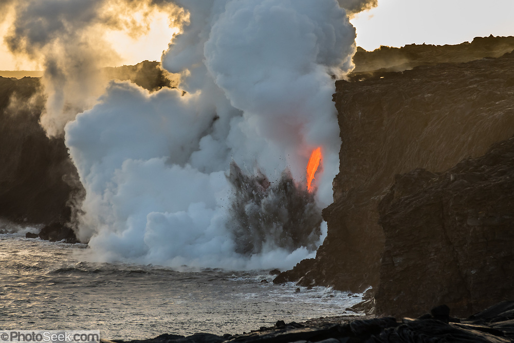 Glowing lava exits a lava tube, jets into the ocean, and explodes at Kamokuna, enlarging the Big Island, in Hawaii Volcanoes National Park, just west of Kalapana, Hawaii, USA, on February 1, 2017. On Kilauea volcano's south flank, Pu'u O'o crater has been erupting continuously since 1983, making it the world's longest-lived rift-zone (flank) eruption of the last 200 years. The eruption has consumed 189 buildings and 8.7 miles of highway. Since 1987, the coastal highway has been closed, buried under lava up to 115 feet thick. After June 30, 2016, the County of Hawaii opened a section of the emergency road/Highway 130 to lava viewing (8 miles round trip, open 3pm-9pm), limiting vehicles to bicycles (rented at the roadblock in Kalapana for $15+ for 3 hours), local residents' cars, and emergency vehicles. See updates at: USGS Hawaiian Volcano Observatory (HVO) http://hvo.wr.usgs.gov and www.hawaiicounty.gov/lava-viewing/. Kilauea is between 300,000 and 600,000 years old and emerged above sea level about 100,000 years ago.