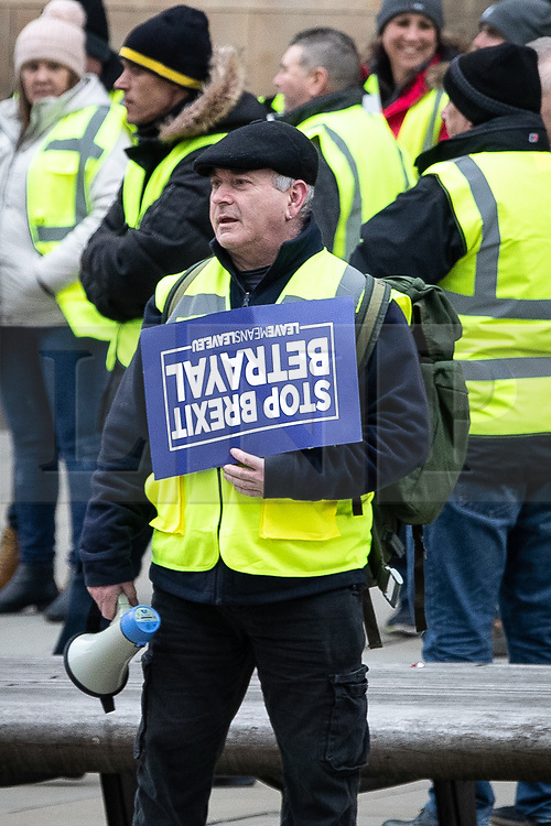 """© Licensed to London News Pictures . 05/01/2019. Manchester, UK. A man carrying a Stop Brexit Betrayal placard . A Yellow Vest demonstration takes place in St Peter's Square in central Manchester . The protest was organised via YouTube account """" Tommy Robinson News """" and was called in the wake of stabbings at Manchester Victoria Train Station on New Year's Eve . Protesters chanted in favour of Brexit , against police and press and carried pro-Trump and EDL clothing and placards . Photo credit : Joel Goodman/LNP"""