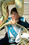 Band member age 16 looking thru tuba during football game.  Minneapolis Minnesota USA