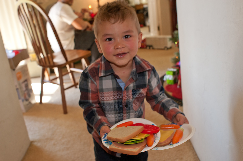 young boy smiling at camera, holding two plates with toy-sandwiches and carrots