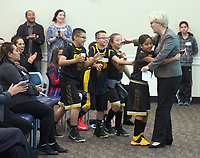 Members of Gil Basketball Academy give Carol Larson, president and CEO of The David and Lucile Packard Foundation a hug at the December 5th, 2017 opening of the Stories from Salinas exhibition at the CSUMB Salinas Center for Arts and Culture in Oldtown. The exhibition celebrates the mentors, youth and families of the Salinas Youth Initiative.