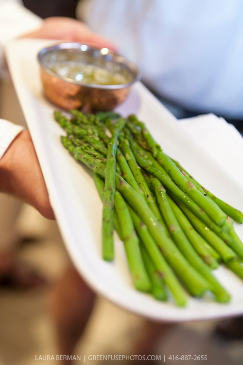 Tender spring Asparagus on a white  plate with a copper bowl of butter.