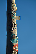 Low angle view of a house frontal totem pole against a blue sky at the Haida Heritage Centre and museum near Skidegate, Haida Gwaii, British Columbia.