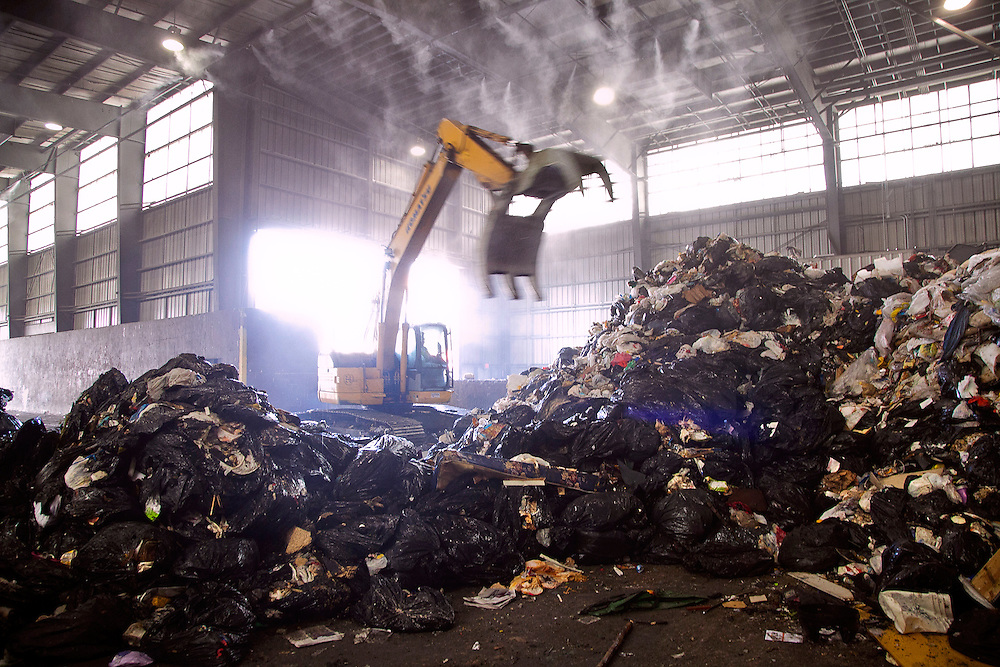 Track-hoe claw graps at pile of solid waste on tipping floor of waste transfer station