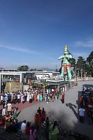 Hindus worshipping under giant statue of Hanuman (Monkey God) at Batu Caves.