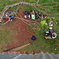 Cathy sits around the tree house of a Boy Scouts Camp in Mathere as she listens to the stories of youth artists and young women soccer players who have been participating in the sports and arts empowerment program called the Mt. Kenya Marvelous Fraternity.  Nearly 3,700 young people have been trained in volunteer leadership through the program.