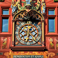 Rathaus Town Hall Clock in Basel, Switzerland <br /> This beautiful clock was added to the Rathaus Town Hall in 1512.  On the left holding a church building is Heinrich II who was King of Germany and then Italy before becoming the Holy Roman Emperor in the early 11th century.  On the right with a cross is his wife, Cunigunde of Luxembourg.  In the center is Justitia, the crowned Lady of Justice.  The Latin phrase translates into &ldquo;Renovated into a large church in 1901.&rdquo;