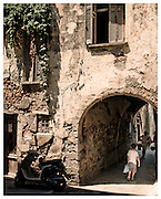 Children walking through archway below Venetian period house in Chania, Crete, Greece.