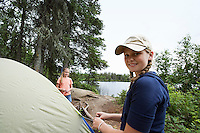 Two teenage girls standing by tent near lake, portrait