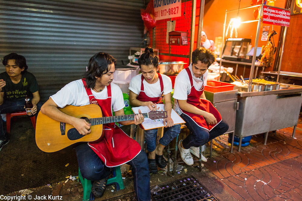 18 SEPTEMBER 2013 - BANGKOK, THAILAND: Waiters in a restaurant in the Chinatown section of Bangkok play guitar and sing during their break. Thailand in general, and Bangkok in particular, has a vibrant tradition of street food and eating on the run. In recent years, Bangkok's street food has become something of an international landmark and is being written about in glossy travel magazines and in the pages of the New York Times.      PHOTO BY JACK KURTZ
