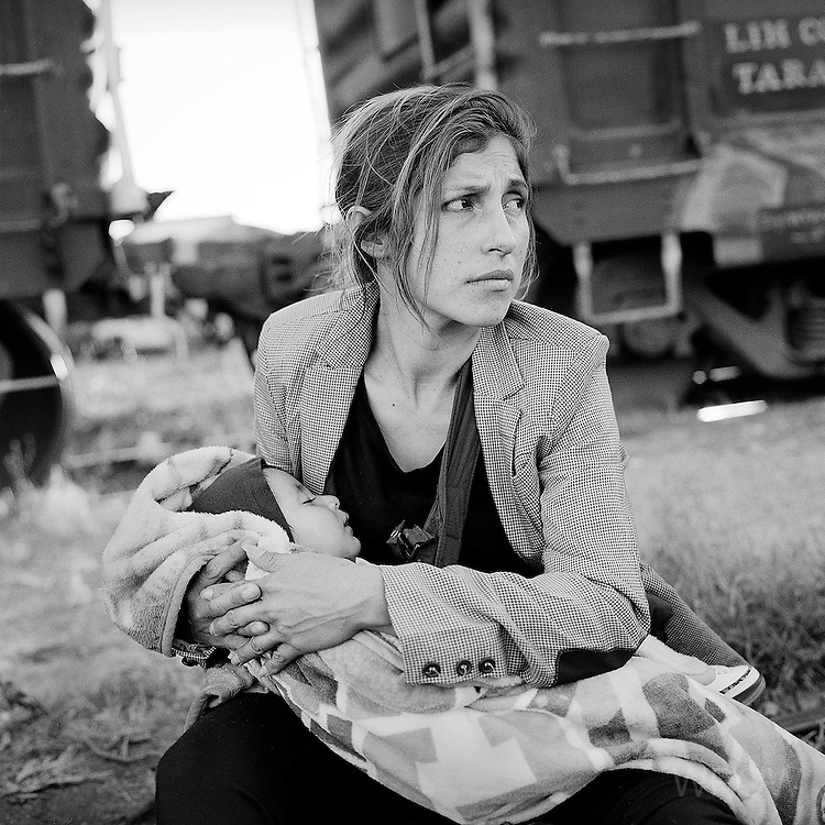 A Guatemalan migrant holds her 6-month-old infant son while waiting to board a northbound cargo train in the railhead town of Arriaga in the southern Mexican state of Chiapas. (photo by Michelle Frankfurter)