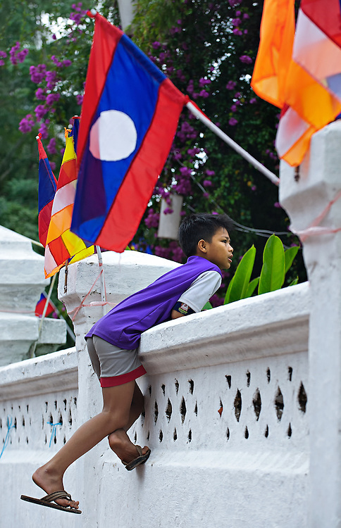A boy gains a good view of a festival in Luang Prabang, Laos.