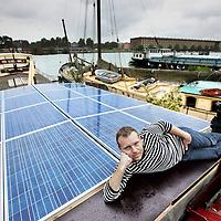 Nederland, Amsterdam , 27 augustus 2010..Hugo Niesing op zijn woonboot met gesubsidieerde zonnepanelen op Borneokade..Duurzaamheidsbijlage..Houseboat with subsidized solar panels.