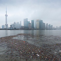 China, Shanghai, Vast pool of trash floats past skyline of Pudong District beneath low clouds along Huangpu River on winter morning