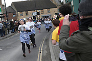 UNITED KINGDOM, Olney: 25 February 2020 <br /> The world's oldest pancake race takes place in the small market town of Olney, Buckinghamshire. It is said to have originated in 1445 when, according to tradition, a woman of Olney ran to the church after hearing the shriving bell, still dressed in her apron  and still clutching her frying pan. <br /> Pictured: Ladies run through the town toward the parish church as they take part in the Olney Pancake Race. Only women who live or work in Olney can take part in the official Olney Pancake Race.