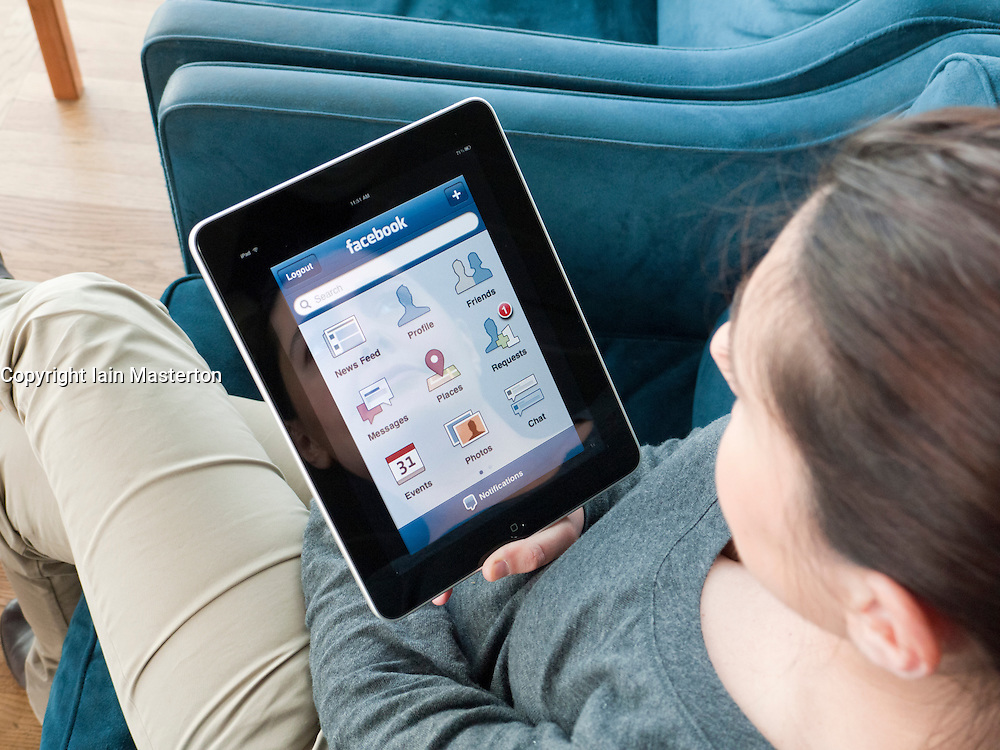 Woman using iPad computer tablet to check Facebook website in airport departure lounge