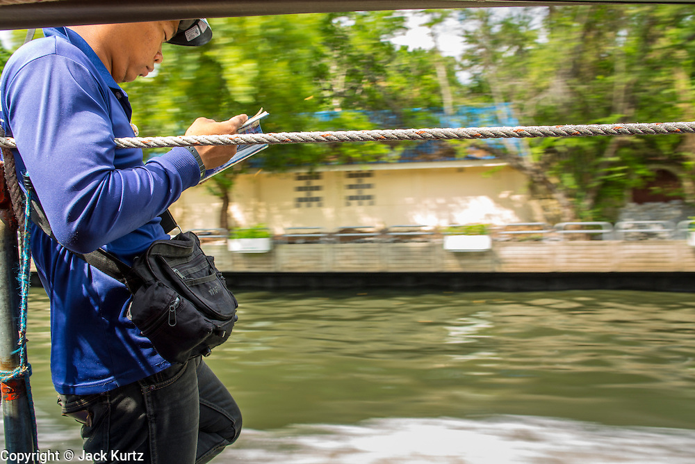 14 NOVEMBER 2012 - BANGKOK, THAILAND: A fare collector reads between stops on a khlong boat on Khlong Saen Saeb in Bangkok. Bangkok used to be criss crossed by canals (called Khlongs in Thai) but most have been filled in and paved over. Khlong Saen Saeb is one of the few remaining khlongs in Bangkok with regular passenger boat service. Boats and ships play an important in daily life in Bangkok. Thousands of people commute to work daily on the Chao Phraya Express Boats and fast boats that ply Khlong Saen Saeb. Boats are used to haul commodities through the city to deep water ports for export.      PHOTO BY JACK KURTZ