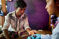 Young miner Htay Maung has a blood test for malarial conducted by Save the Children volunteer Nay Zaw Htwe at Nang Hein Goldmine Homalin Township North Eastern Myanmar 2017.<br /> There are up to two hundred mines in the area where workers are paid $US 10 a day. Malaria was as high as 60% in 2011. In 2017 it is 4% after a Save the Children Malarial treatment and prevention program. In the mining communities there is heavy drug use.
