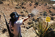 On the desert shooting range, a young woman competes in the 3-gun match.  Soldier of Fortune Convention, Las Vegas.