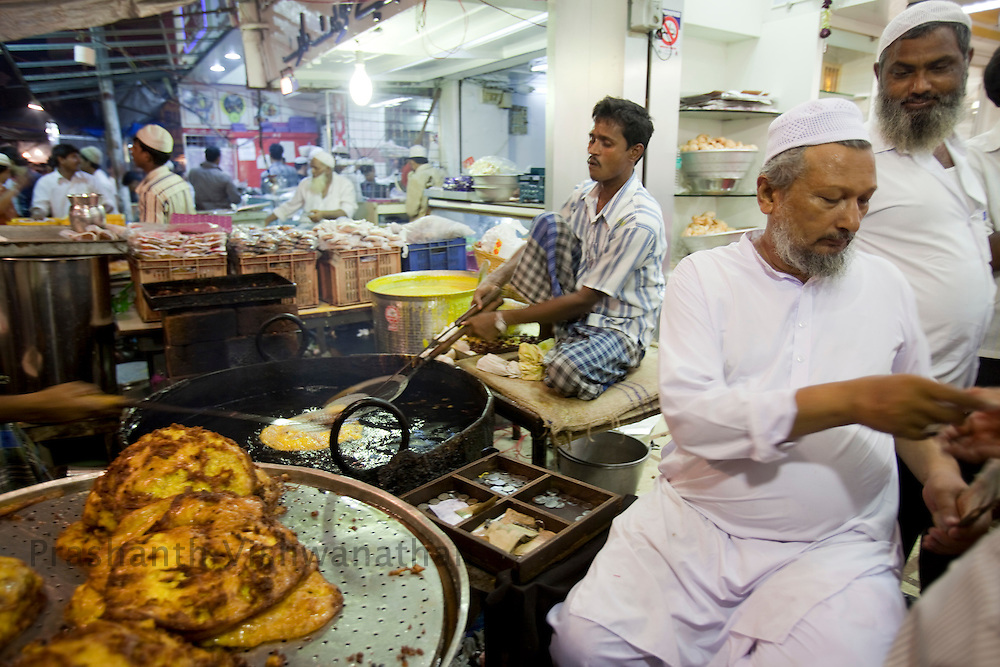 "Abdul Rehman Nasir Khan (R) overlooks as ""Malpua"" a sweet pancake dish is made at a stall, opposite Minara masjid at Mohammed Ali road in Mumbai, Maharashtra, India, on Saturday September 6, 2009. Photographer: Prashanth Vishwanathan/The National"