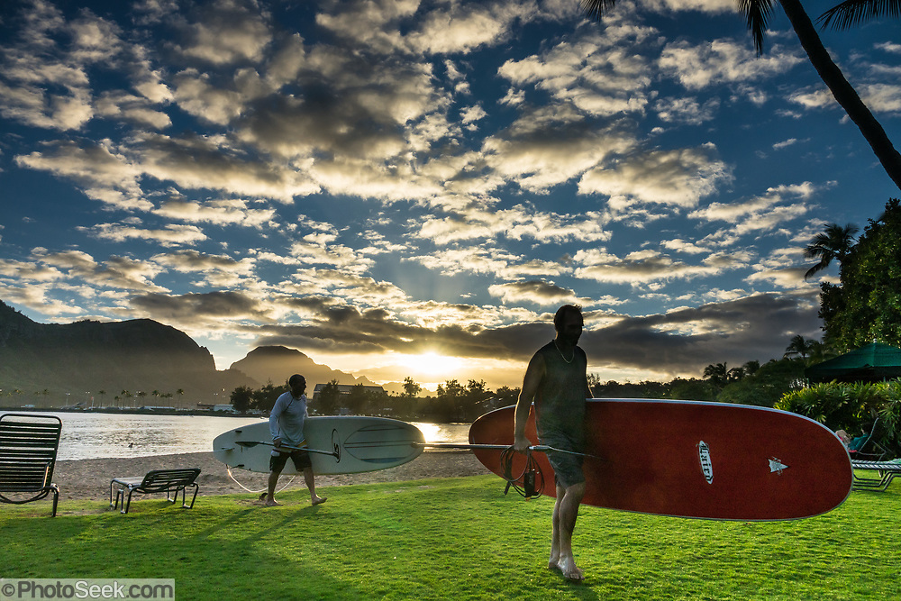 A golden sunset shines between two men carrying surfboards from Nawiliwili Beach, at Kauai Marriott Resort, Lihue, island of Kauai, Hawaii, USA. For this photo's licensing options, please inquire.