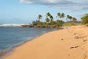 A lone person stands on Ali'i Beach on the North Shore of Oahu.