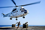 Marines assigned to Combat Cargo run to safety after attaching a hoist to an SA330J Puma helicopter from the Military Sealift Command dry cargo and ammunition ship USNS Richard E. Byrd (T-AKE 4) from the flight deck of the amphibious assault ship USS Makin Island (LHD 8) during a vertical replenishment. Makin Island and embarked Marines assigned to the 11th Marine Expeditionary Unit (11th MEU) are deployed supporting maritime security operations and theater security cooperation efforts in the U.S. 5th Fleet area of responsibility. (U.S. Navy photo by Chief Mass Communication Specialist John Lill/Released)